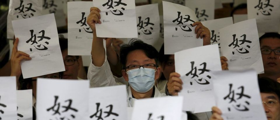 "Doctors hold placards reading the Chinese character for ""Anger"""
