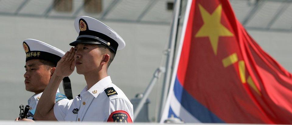A PLA Navy sailor salutes as sailors disembark the PLAN replenishment ship Gaoyouhu at Joint Base Pearl Harbor Hickam