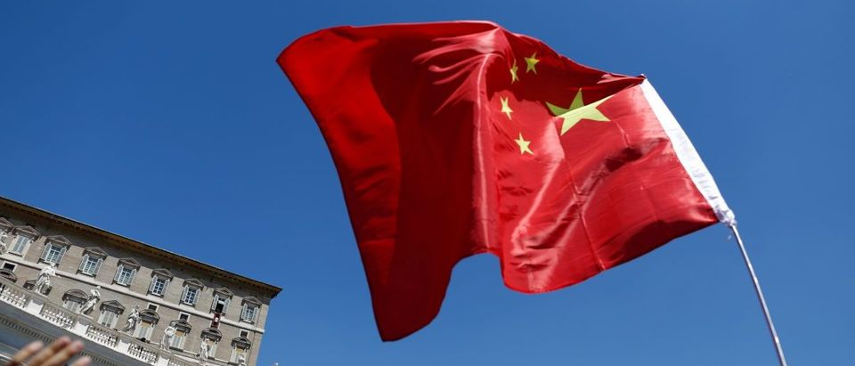 A man waves a Chinese flag as Pope Francis leads his Sunday Angelus prayer in Saint Peter's square at the Vatican