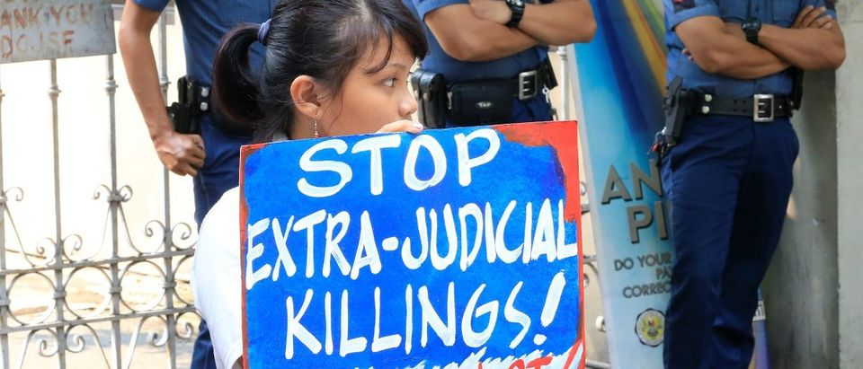 Anti-riot policemen stand guard in front of a protester holding a placard condemning the rise in extrajudicial killings in connection to the war on illegal drugs during a protest outside the Department of Justice in metro Manila