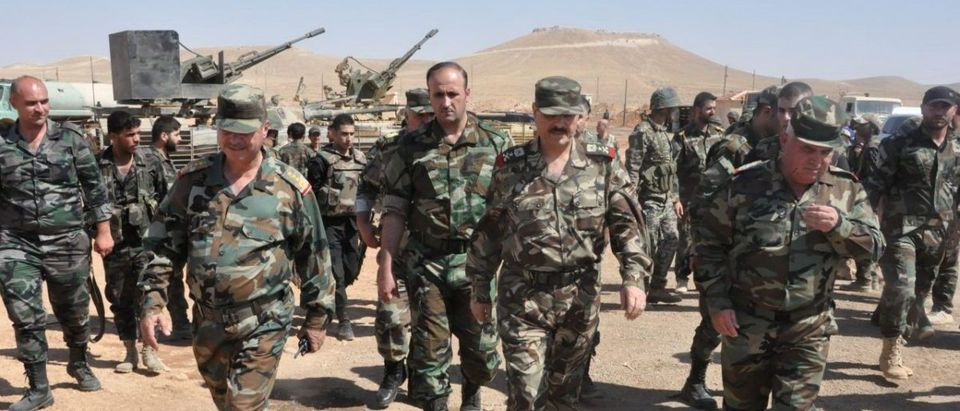 Syrian Minister of Defense, Fahd Jassem al-Freij, walks during a visit to Syrian regime soldiers in Aleppo