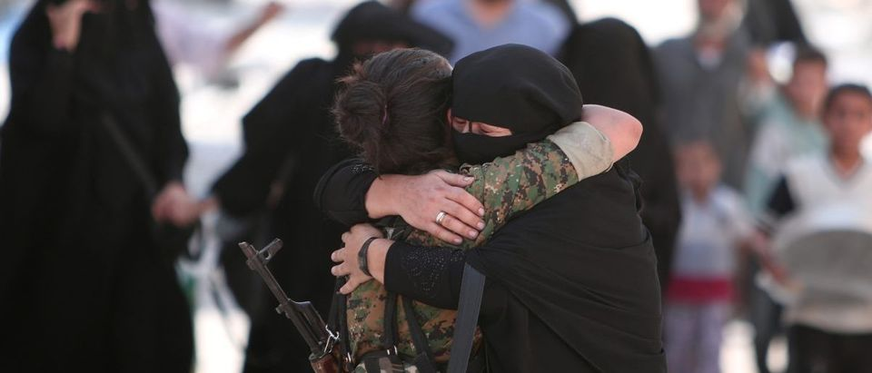 A woman embraces a Syria Democratic Forces (SDF) fighter after she was evacuated with others by the SDF from an Islamic State-controlled neighborhood of Manbij (Reuters Pictures)