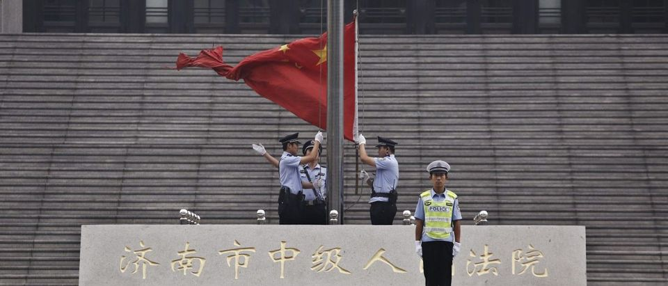 Policemen hoist a Chinese national flag in front of an entrance of a Chinese court