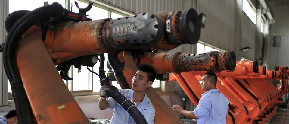 Workers fix second-hand robots in a factory in Shanghai