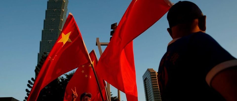 Pro-China supporters hold Chinese national flags in front of landmark building Taipei 101, outside the dinner venue of Sha Hailin, a member of Shanghais Communist Party standing committee, in Taipei, Taiwan