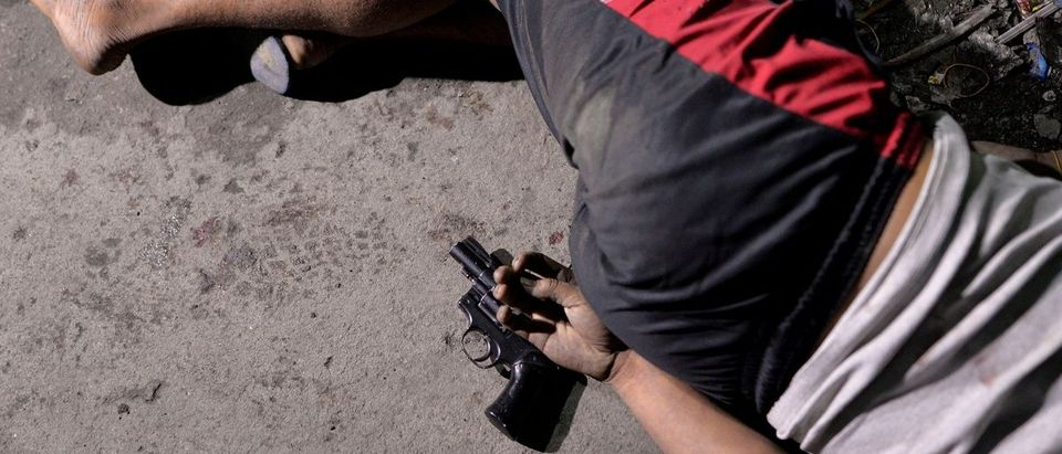 """The body of a man is pictured with a gun under his hand, whom police said was killed during a drug bust operation on """"Shabu"""" (Meth), in Manila"""