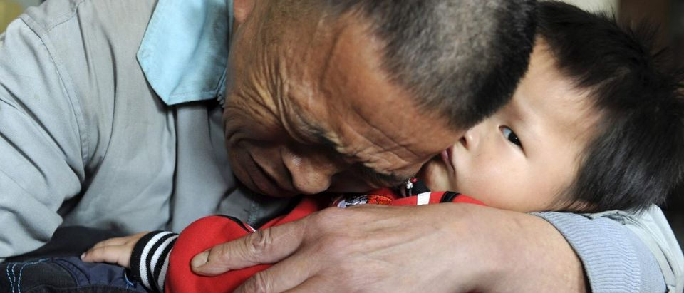 Wang Bangyin, a local farmer, holds his rescued son after the pair were reunited at Guiyang Welfare Centre for Children in Guiyang