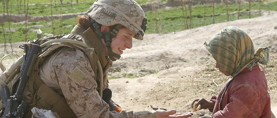 U.S. Marine Corps handout photo of Lt. Johanna Shaffer sharing a cookie with an Afghan child in Farah Province