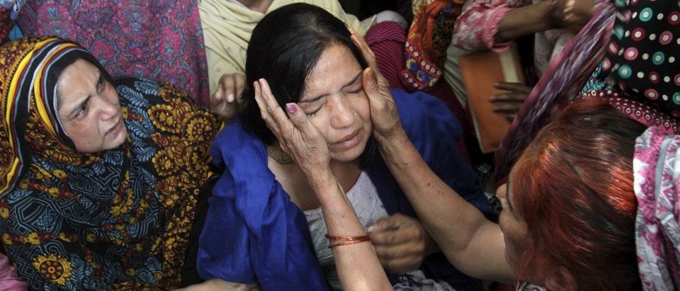 Family members comfort a woman mourns the death of a relative, who was killed in a blast outside a public park on Sunday, during funeral in Lahore,