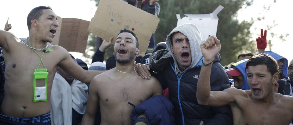 Migrants protest as they wait to cross the border from Greece into Macedonia