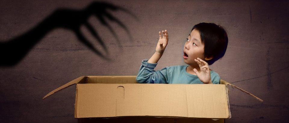 Scared boy in box (Shutterstock/Hung Chung Chih)