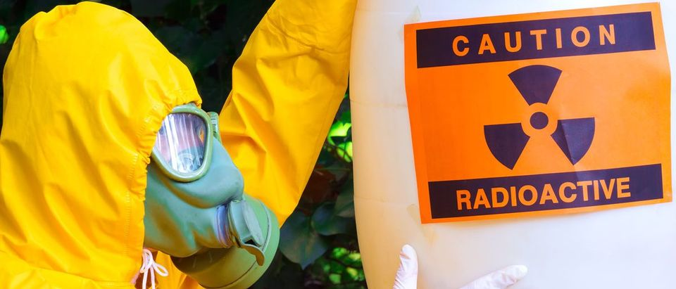 Radioactive waste ; Chemist in protective suit the disposal of radio active waste. (Shutterstock/overcrew)