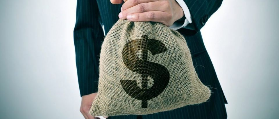 Businessman holding a burlap money bag. [Shutterstock - nito - 189871454]