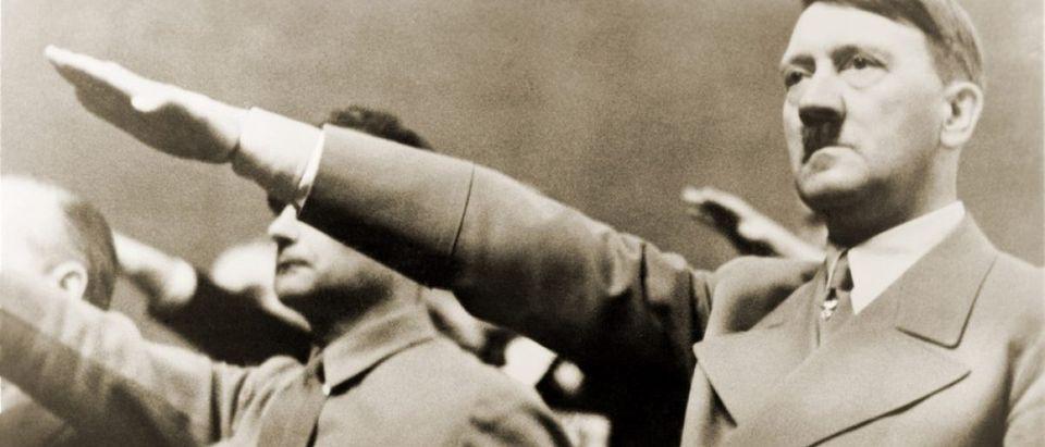 Adolf Hitler, giving Nazi salute. To Hitler's right is Rudolph Hess. 1939. (Credit: Everett Historical / Shutterstock.com)