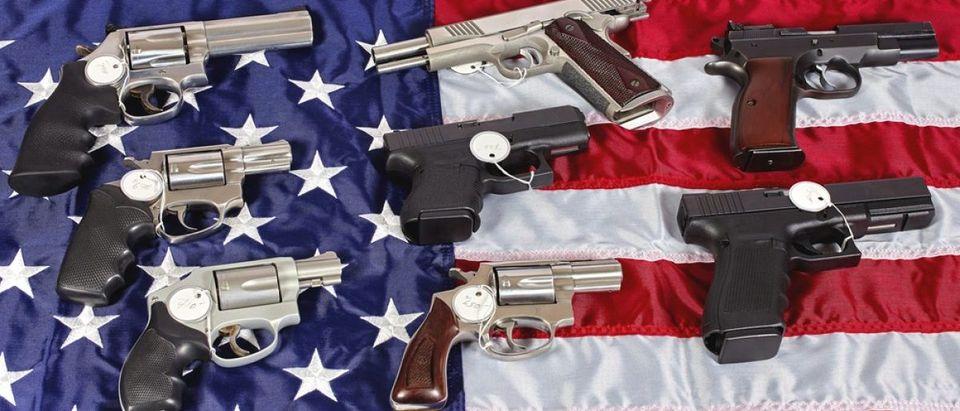 Guns on the American flag. Copyright: ja-images/Shutterstock.com