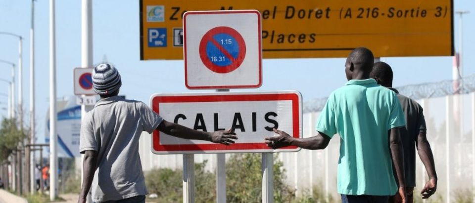 "Migrants pass by a road sign as they leave the northern area of the camp called the ""Jungle"" in Calais"