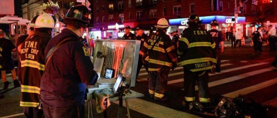 New York City police and firefighters stand near the site of an explosion in the Chelsea neighborhood of Manhattan, New York