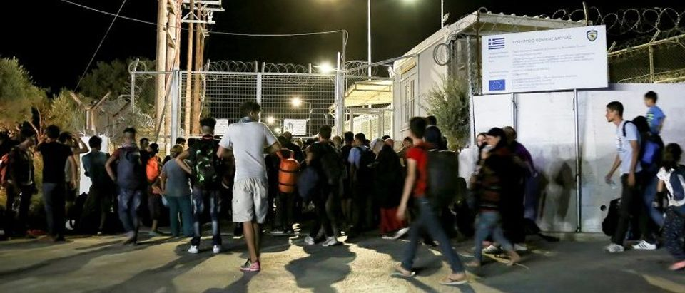 Refugees and migrants stand at the closed gate of the Moria migrant camp, after a fire at the facility, on the island of Lesbos