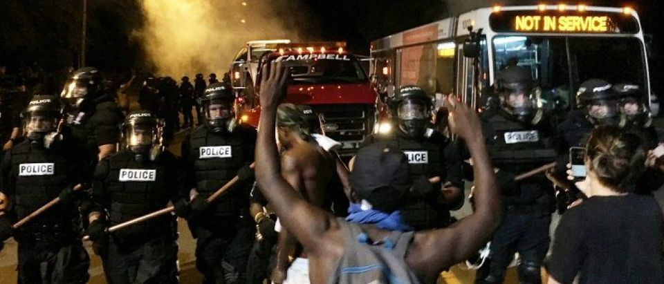 Police officers wearing riot gear block a road during protests after police fatally shot a man in the parking lot of an apartment complex in Charlotte