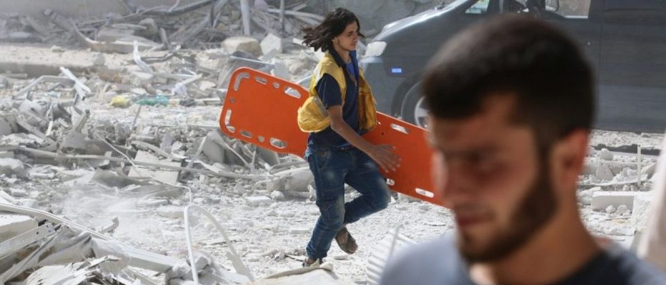 A man runs with a stretcher in a damaged site after airstrikes on the rebel held al-Qaterji neighbourhood of Aleppo, Syria September 21, 2016. REUTERS/Abdalrhman Ismail