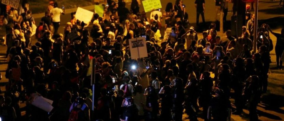 Demonstrators protest the police shooting of Keith Scott next to riot police at a highway onramp in Charlotte, North Carolina, U.S., September 24, 2016. REUTERS/Mike Blake
