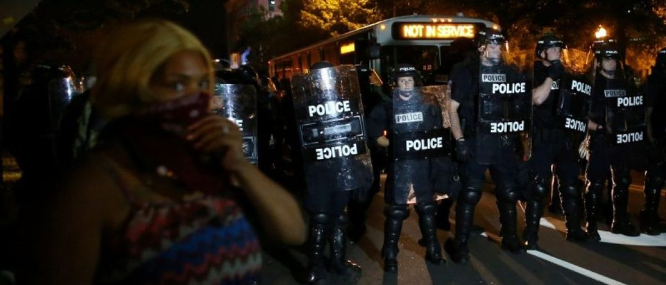 A demonstrator is greeted by police in riot gear while continuing to protest after curfew in Charlotte, North Carolina, U.S., September 25, 2016. REUTERS/Mike Blake