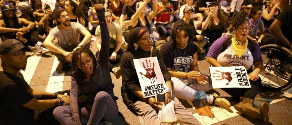 Protesters sit and hold a moment of silence for Keith Scott during another night of protests over the police shooting of Scott in Charlotte, North Carolina, U.S. September 24, 2016. REUTERS/Mike Blake