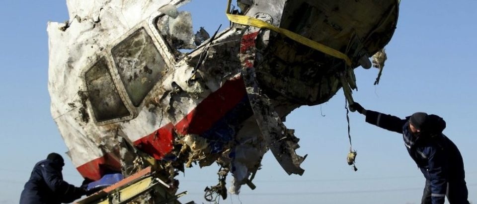 Local workers transport a piece of the Malaysia Airlines flight MH17 wreckage at the site of the plane crash near the village of Hrabove (Grabovo) in Donetsk region