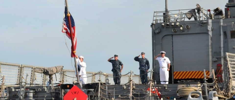 Sailors salute colors.
