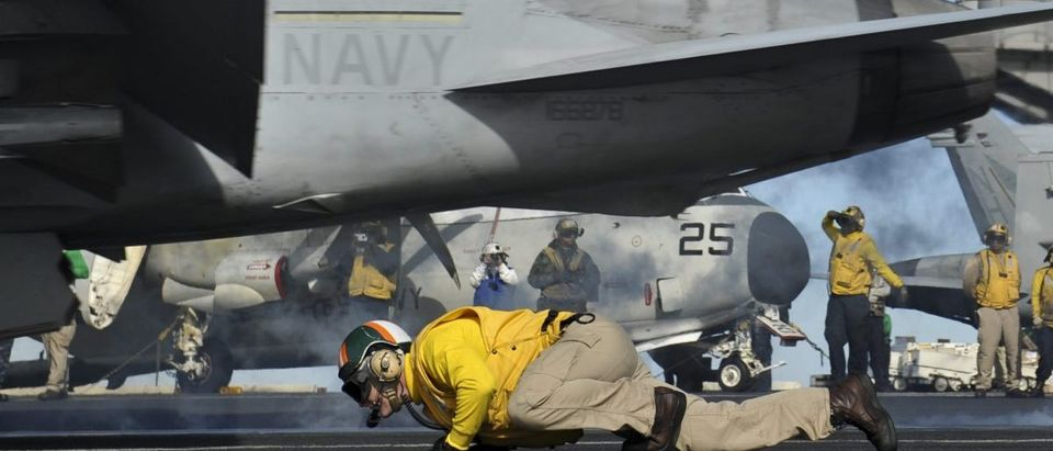An officer ducks as an F/A-18F launches.