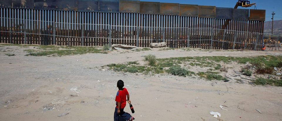 A boy looks at a fence that is part of a section of the U.S.-Mexico border wall at Sunland Park, U.S. opposite the Mexican border city of Ciudad Juarez