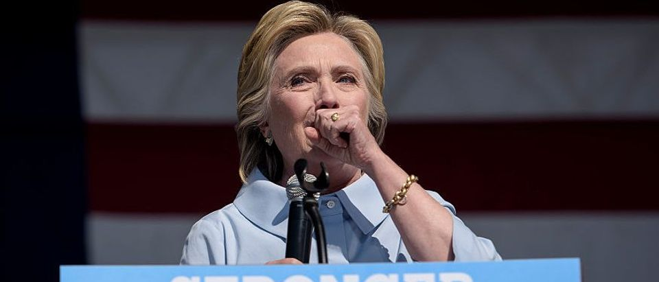 Democratic presidential nominee Hillary Clinton coughs during a Labor Day rally September 5, 2016 in Cleveland, Ohio. Hillary Clinton launched the home stretch of her US presidential bid aiming to solidify her advantages over rival Donald Trump, with both candidates converging on working-class Ohio as ground zero of their 2016 campaign battle