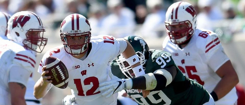 Alex Hornibrook #12 of the Wisconsin Badgers is grabbed by Raequan Williams #99 of the Michigan State Spartans as he runs downfield during the game at Spartan Stadium on September 24, 2016 in East Lansing, Michigan