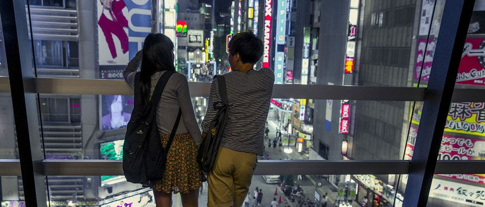 A couple overlooks Shinjuku's nightlife district of Kabukichoi in Tokyo