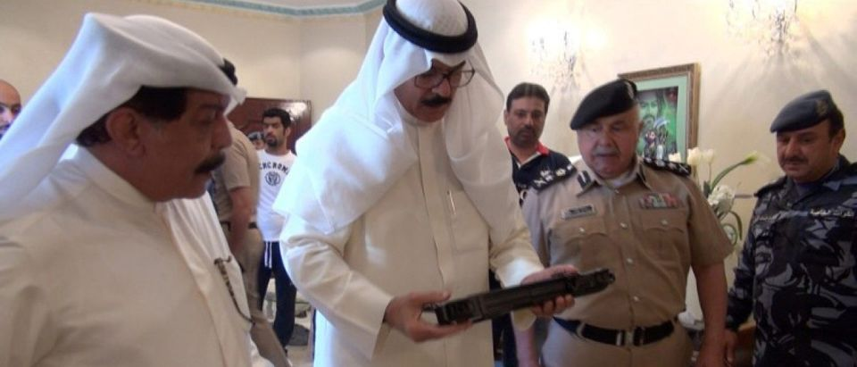 Kuwait's Deputy Prime Minister and Interior Minister Sheikh Mohammad al-Hamad al-Sabah look at weapons that Kuwaiti authorities said were smuggled from Iran by suspected members of a militant cell in Kuwait