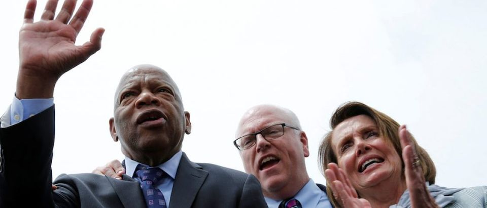 U.S. House Minority Leader Nancy Pelosi (D-CA) (R) applauds as Rep. John Lewis (D-GA) (L) waves to supporters along with House Democrats after their sit-in over gun-control law on Capitol Hill in Washington, U.S., June 23, 2016. REUTERS/Yuri Gripas