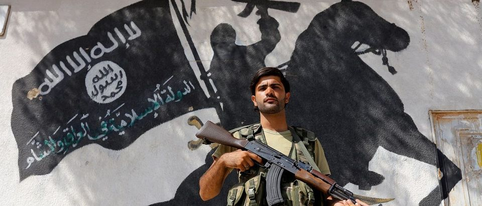 A member of Turkish-backed Free Syrian Army stands guard in front of a building in the border town of Jarablus