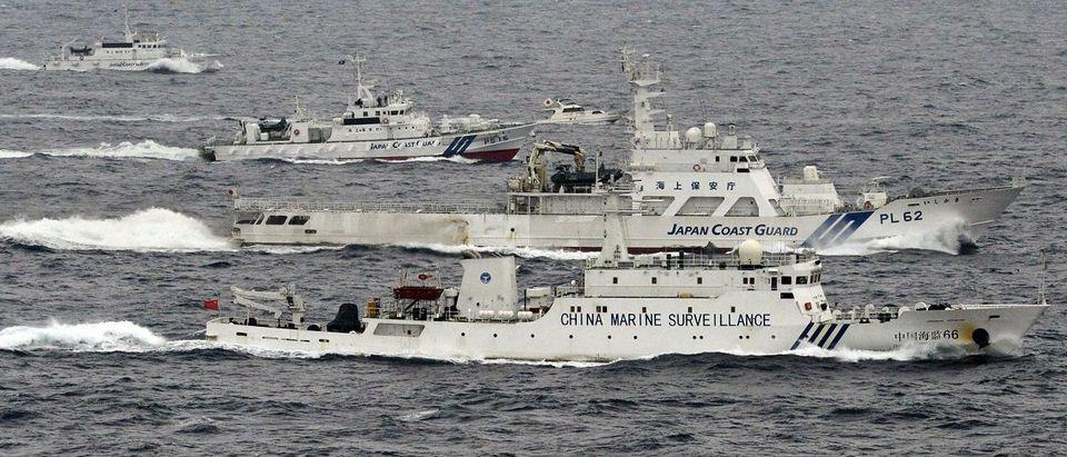 An aerial photo shows a Chinese marine surveillance ship Haijian No. 66 cruising next to Japan Coast Guard patrol ships in the East China Sea