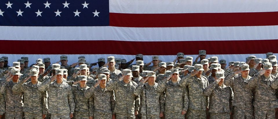 U.S. soldiers salute during a mass reenlistment ceremony in a U.S. military camp in Balad