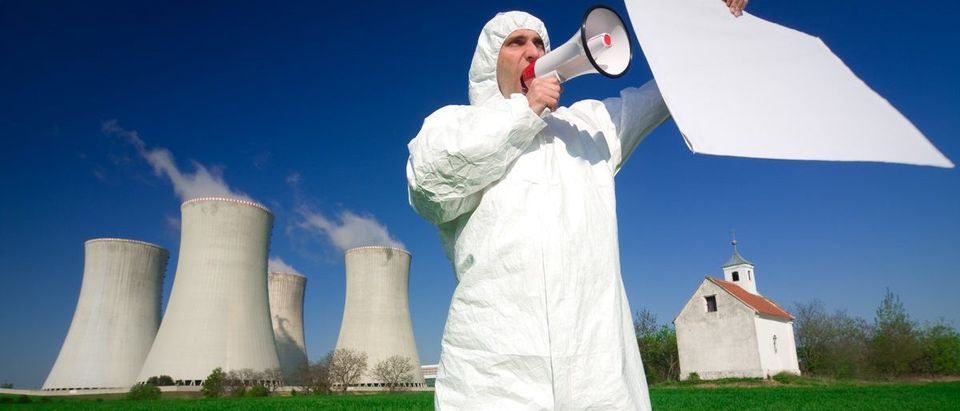 A environmental activist protesting with a blank banner in front of nuclear power plant. (Shutterstock/Rene Jansa)