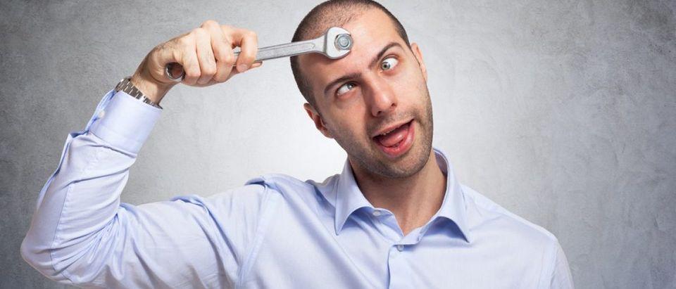 Funny man using a wrench to fix his brain. (Credit: Minerva Studio/Shutterstock)