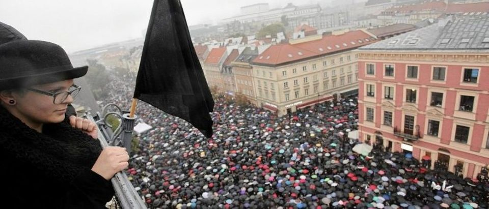A woman observes thousands of people during an abortion rights campaigners' demonstration to protest against plans for a total ban on abortion in front of the Royal Castle in Warsaw