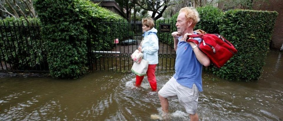 Residents of an upscale historic neighborhood wade through flood waters as they return to their home after Hurricane Matthew hit Charleston, South Carolina