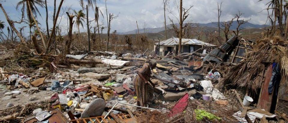 A woman walks on debris in an area devastated by Hurricane Matthew in Port-a-Piment, Haiti