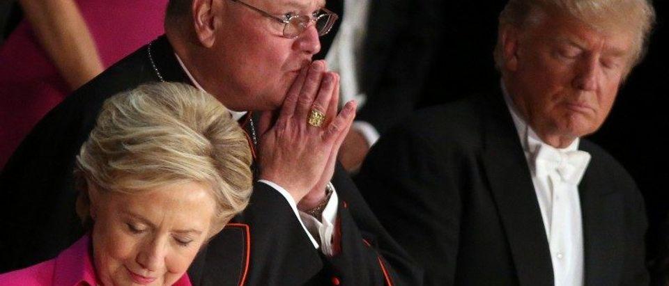 New York Cardinal Timothy Dolan prays accompanied by Democratic U.S. presidential nominee Hillary Clinton and Republican U.S. presidential nominee Donald Trump in New York