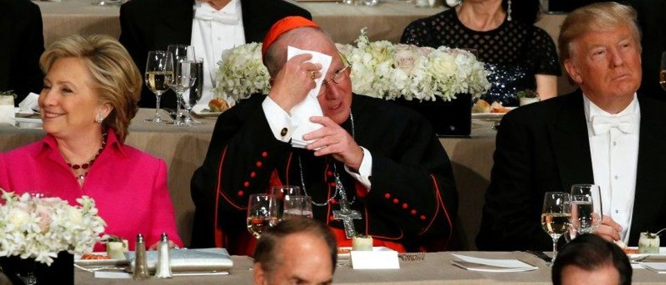 Dolan mops his brow as he takes his place between Clinton and Trump during the Alfred E. Smith Memorial Foundation dinner in New York