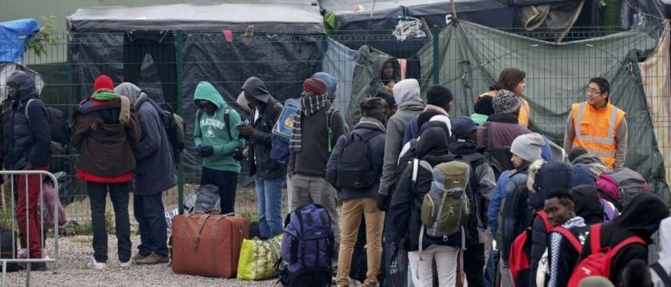 "Migrants with their belongings queue at the start of their evacuation and transfer to reception centers in France, and the dismantlement of the camp called the ""Jungle"" in Calais"