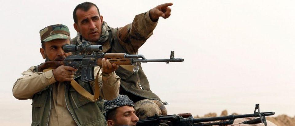 A Kurdish Peshmerga fighter aims to fire during a battle with Islamic State militants at Topzawa village, near Bashiqa