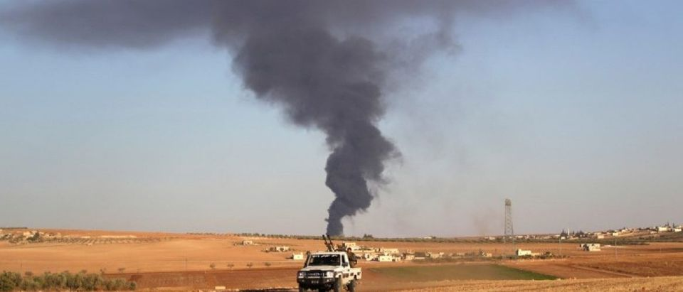 Rebel fighters ride a military vehicle near rising smoke from al-Bab city, northern Aleppo province
