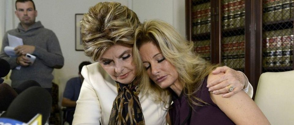 Summer Zervos is embraced while speaking to reporters about allegations of sexual misconduct against Donald Trump during a news conference in Los Angeles